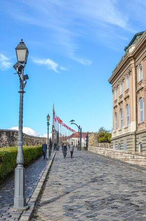 Budapest, Hungary - Nov 6, 2019: Cobbled path along with the Buda Castle palace buildings. Historical palace building, facade with arched windows. Tourist attraction and Hungarian national heritage.
