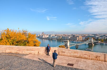 Budapest, Hungary - Nov 6, 2019: Older Asian couple taking travel pictures on the viewpoint above the Hungarian city. Danube river, Hungarian parliament building and Szechenyi Bridge in background. 報道画像