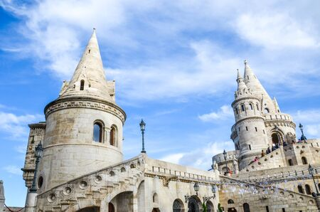 Fishermans Bastion in Budapest, Hungary. Major tourist attraction of the Hungarian capital city. Fairy tale monument, built in Neo-Romanesque style. Blurred people on the stairs walking to the tower.