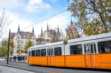 Budapest, Hungary - Nov 6, 2019: Public yellow tram riding in front of the Hungarian Parliament building. Hungarian capital city public transport. City transportation. Tourist attraction.