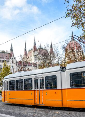 Budapest, Hungary - Nov 6, 2019: Public yellow tram riding in front of the Hungarian Parliament building. Hungarian capital city public transport. City transportation. Eastern European destinations.