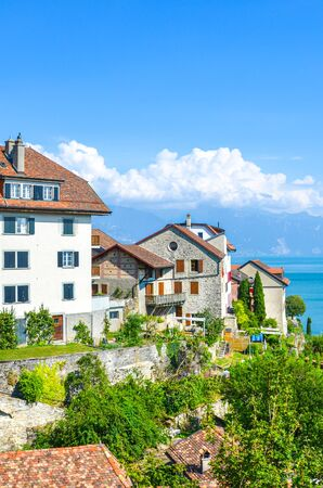 Rivaz, Switzerland - July 9, 2019: Beautiful winemaking village Rivaz in Swiss Lavaux wine region. Buildings located by the stunning Lake Geneva. Natural landscape. European travel destination.