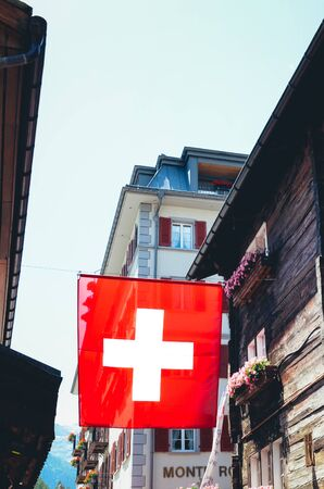 Zermatt, Switzerland - July 10 2019: National flag of Switzerland waving on the street in the popular Alpine resort. Swiss flag. White cross in the center of a square red field. Switzerland concept. 報道画像