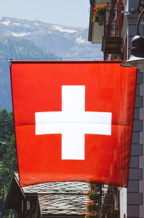 Zermatt, Switzerland - July 10 2019: National flag of Switzerland waving on the street in the popular Alpine resort. Swiss flag. White cross in the center of a square red field. Swiss concept.