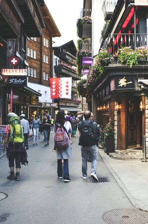 Zermatt, Switzerland - July 10, 2019: Street with tourists in beautiful Alpine village Zermatt in the summer season. The city center with people. Shops, cafes and restaurants. 報道画像