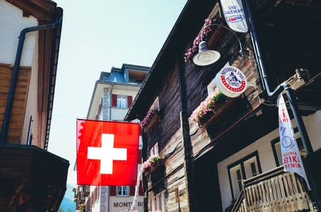 Zermatt, Switzerland - July 10, 2019: National flag of Switzerland waving on the street in the popular Alpine resort. Swiss flag. White cross in the center of a square red field. Swiss concept.