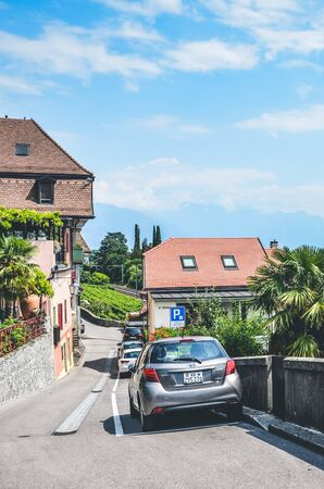 St. Saphorin, Switzerland - July 9, 2019: Street in rural winemaking village Saint Saphorin in Swiss Lavaux wine region. Houses located on the slope above the beautiful Geneva Lake. Natural landscape.