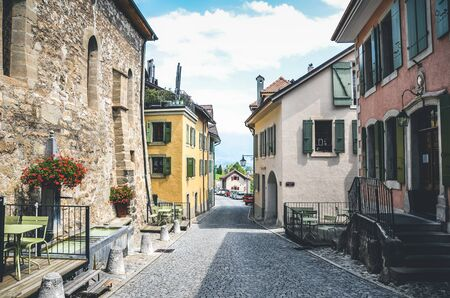 Saint Saphorin, Switzerland - July 9, 2019: Historical street in picturesque winemaking village St. Saphorin in Swiss Lavaux wine region. Traditional houses, cobbled streets. Outdoor restaurants.