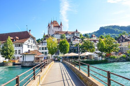 Thun, Switzerland - August 8, 2019: Amazing cityscape of historical city Thun. Located not far from the Swiss Alps. The dominant is the famous Thun castle. Bridge over turquoise Aare river. 報道画像