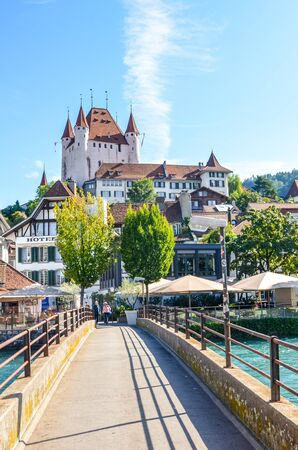 Thun, Switzerland - August 8, 2019: Amazing view of historical city Thun. Located not far from the Swiss Alps in Bernese region. The dominant is famous Thun castle. Bridge over turquoise Aare river.