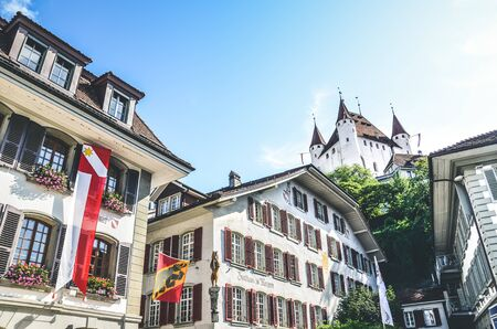 Thun, Switzerland - August 8, 2019: Historical center of the Swiss city Thun. The dominant of the old town is the famous Thun castle on the hill in the background. European travel destination. 報道画像
