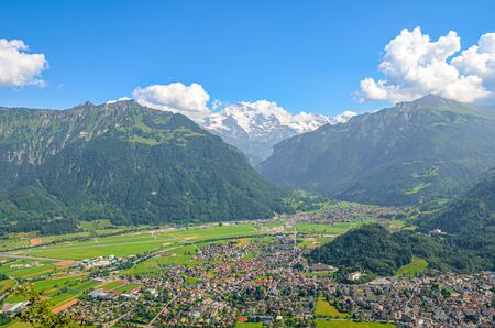 Stunning view of Interlaken and adjacent mountains photographed from the top of Harder Kulm in Switzerland. Swiss Alps landscape. City in the Alpine valley surrounded by mountains. Sunny day.