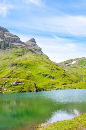 Amazing Bachalpsee lake in the Swiss Alps photographed in the summer season. Alpine lake and landscape. Popular landmark on the hiking path from Grindelwald. Tourist places in Switzerland.