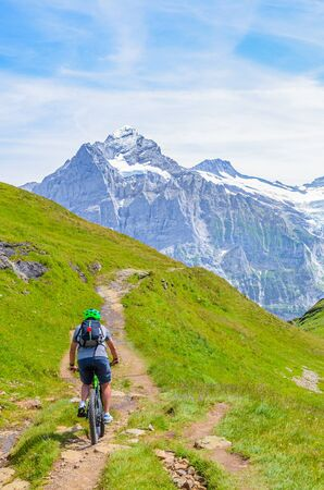 Mountain biker riding in amazing summer Alpine landscape. Snowcapped mountains in the background. Photographed on the trail from Grindelwald to Bachalpsee. Active vacation, people doing sport.