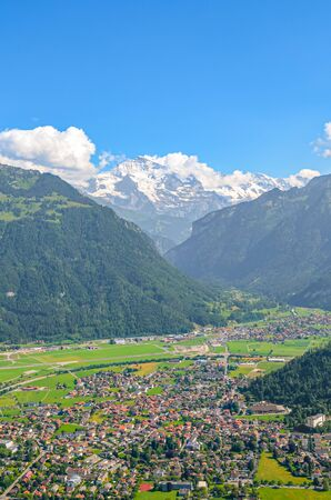 Amazing view of Interlaken and adjacent mountains photographed from the top of Harder Kulm in Switzerland. Swiss Alps landscape. City in the Alpine valley surrounded by mountains. Vertical photo.