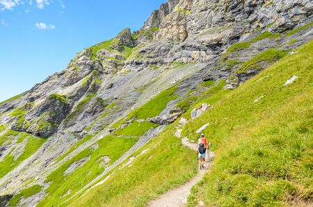 Hiking path in the Swiss Alps photographed in the summer season. Hikers walking the trail in Kandersteg area, Switzerland. Steep mountains in the background. Green Alpine landscape.