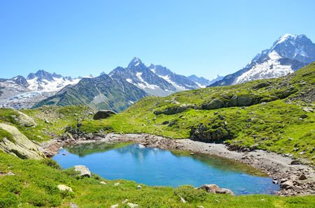 Glacier Lac de Cheserys, Lake Cheserys near Chamonix-Mont-Blanc in French Alps. Alpine lake with snow-capped mountains in the background. Tour du Mont Blanc trail. The Alps in the summer season.