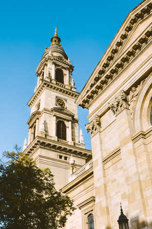 Tower of St. Stephens Basilica in Budapest, Hungary with blue sky above. Historical sample of neoclassical architecture. Tourist landmark in the center of the Hungarian capital city. Vertical photo.