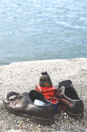 Budapest, Hungary - Nov 6, 2019: Shoes on the Danube Bank. Monument to honour the Jews who were killed by fascists during World War II. Iron shoes, red candle. Blurred Danube in the background. 新聞圖片