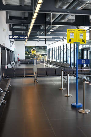 Charleroi, Brussels, Belgium - March 17, 2020: Empty airport terminal in the Belgian airport. Gate with no people. Travel restriction due to coronavirus pandemic. COVID-19 shutdown. Cancelled flights.