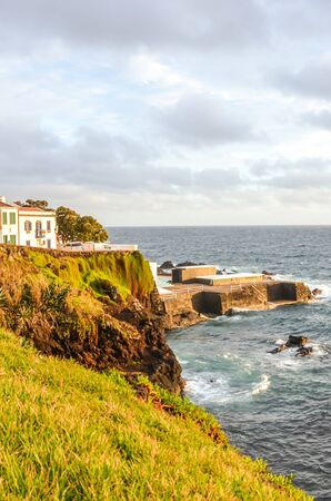 Cliffs by the Atlantic ocean in fishermans village Lagoa, Sao Miguel Island, Azores, Portugal. Traditional houses on the hill above the sea. Sunset light. Vertical photo.
