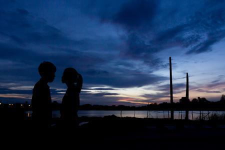 Silhouette couple kissing over sunset background,twilight , blurry, select focus Reklamní fotografie