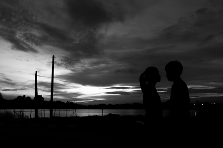 Silhouette couple kissing over sunset background,twilight , blurry, select focus,blackandwhite