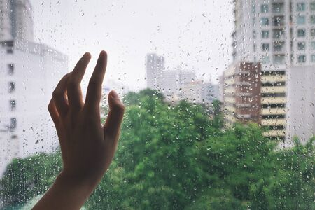 Lonely hand on the mirror during rain