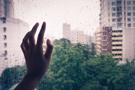 Lonely hand on the mirror during rain,vintage