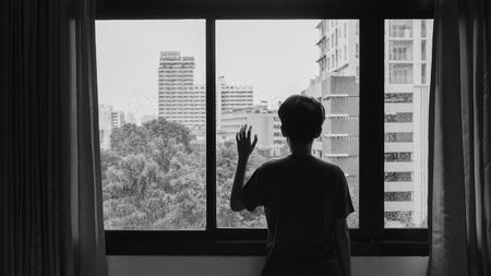gotas de agua: Alguien de pie junto a la ventana con gotas de lluvia en un d�a lluvioso