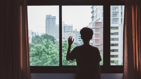uomo sotto la pioggia: Qualcuno in piedi dalla finestra con gocce di pioggia in una giornata piovosa