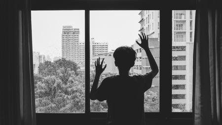 gotas de agua: Alguien de pie junto a la ventana con gotas de lluvia en un día lluvioso