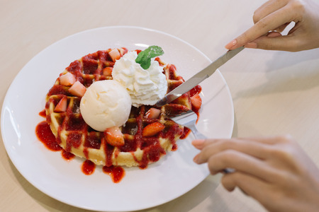 Belgian waffles with ice cream and strawberries ,Hand preparing to eat.