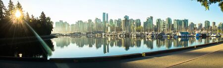 Panoramic view of Vancouver skyline at sunrise as seen from Stanley Park, British Columbia, Canada.