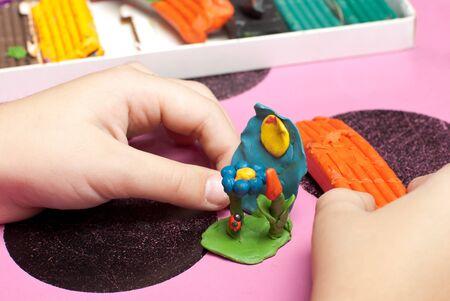 Childrens hands make a plasticine Stock Photo