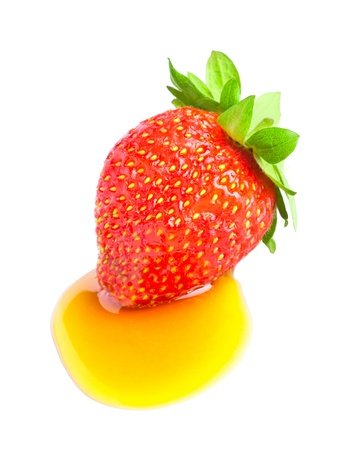 a strawberry with honey, isolated on white photo