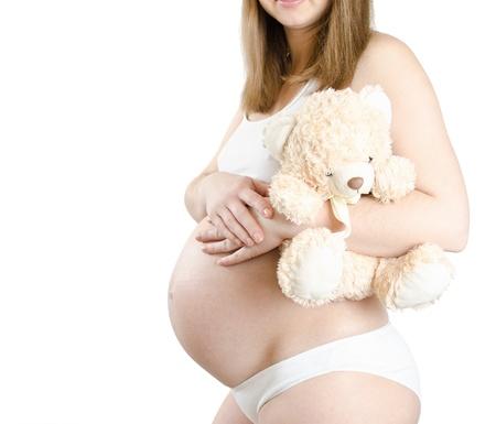 Těhotná žena s medvědem izolovaných na bílém Reklamní fotografie - 13706882