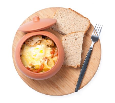 a food in pot on board with bread and fork photo