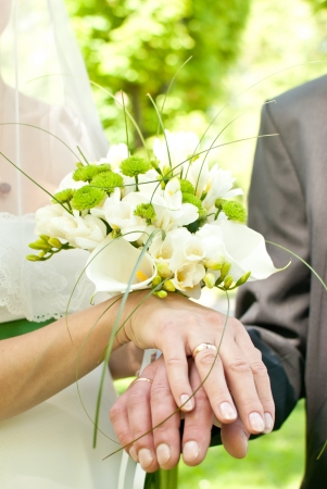 Hands with wedding rings and fower bouquet