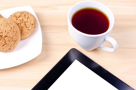 Blank digital black tablet on a desk with epmty whute screen and cup of coffee and plate with cookies Stock Photo - 14027878