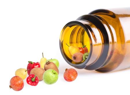 capsula: una fruta y verduras en botella como las vitaminas, sobre fondo blanco, macro