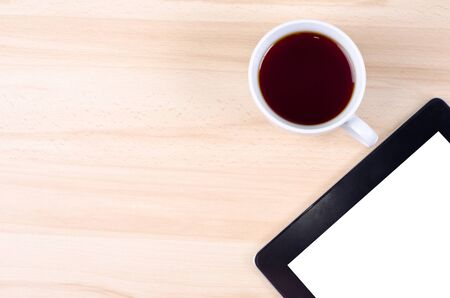 Blank digital black tablet on a desk with epmty whute screen and cup of coffee Stock Photo - 16138591