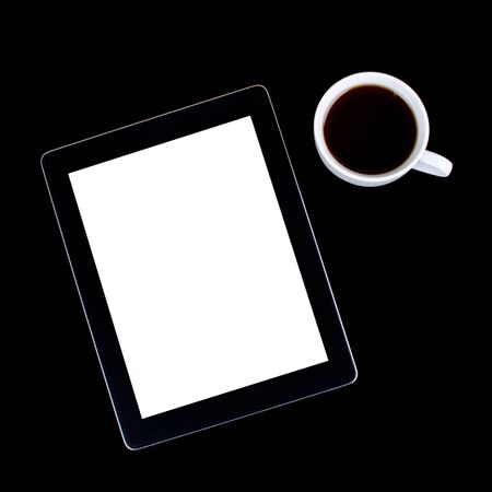 Blank digital black tablet on a desk with epmty whute screen and cup of coffee photo