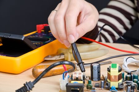chipset: women repairing circuit board with digital multimeter