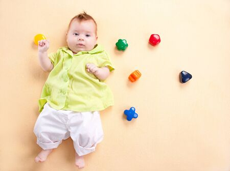 chemise: Newborn baby in green chemise  on yellow background