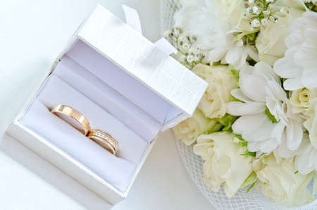 weddingrings: a two golden wedding ring in box with flower on background Stock Photo
