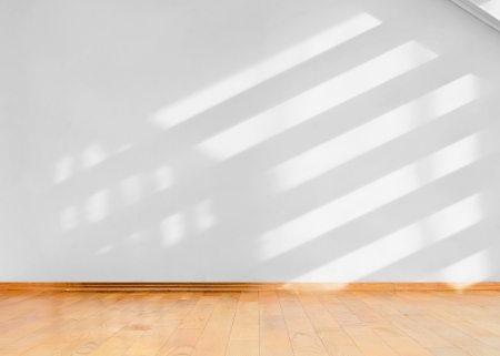 Empty room with wooden floor and diagonal shadows on white wall Stock Photo