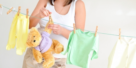 Pregnant woman hanging teddy bear and childrens clothes on rope