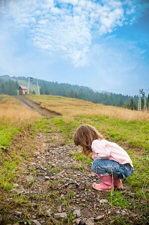kids at the ski lift: girl in a meadow in the mountains