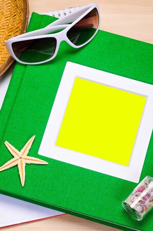 scratchpad: empty green notebook on wooden table surface with beach hat, seashells, starfish, sunglasses